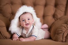 Happy newborn child baby boy with pink cheeks posing on hege retro casual style brown couch divan sofa with big white fur winter w. Arm hat stock photos