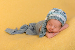Happy newborn sleeping. One week old newborn baby of mixed race sleeping on a soft yellow blanket royalty free stock photos