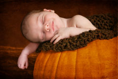 Happy Newborn Sleeping in Pumpkin. Artistic portrait of a newborn baby sleeping in a hollowed out pumpkin. He has a smile on his face. The main color scheme is Stock Photo