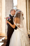Happy newly married couple kissing on street at sunny day Royalty Free Stock Photos