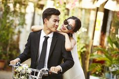 Asian newly wed couple riding a bicycle royalty free stock photography