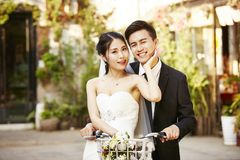 Asian newly wed couple riding a bicycle royalty free stock image