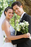 Happy newly wed couple in garden Stock Photo