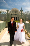Happy newly weds. A happy young newly married couple holding hands, and walking together Royalty Free Stock Image