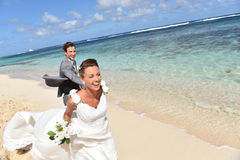 Happy newly-weds running on the caribbean beach Royalty Free Stock Images