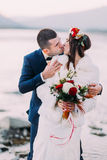 Happy newlywed bridal couple kissing on pebble riverside with forest hills as background Stock Image