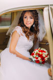 Happy newlywed bride is sitting on a backseat of vintage car Stock Image