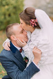 Happy newlywed couple in autumn park. Elegant bride lovingly kissing her handsome new husband in forehead stock photos