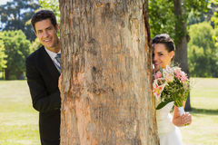 Happy newlywed couple behind tree trunk in park Stock Image