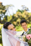 Happy newlywed couple with bouquet in park Royalty Free Stock Photos
