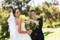 Happy newlywed couple with bouquet in park Stock Photos