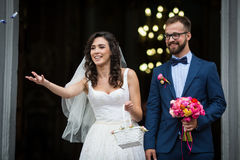 Happy newlywed couple coming out of church, holding bouquet and Stock Photo