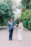 Happy newlywed couple dancing outdoors when walking on park lane holding hands together and laughing Royalty Free Stock Photo