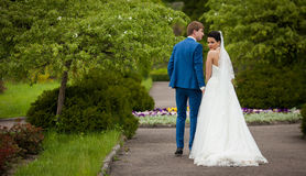 Happy newlywed couple holding hands & walking in park stock image