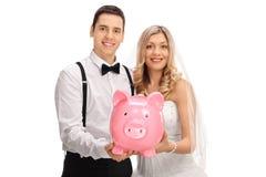 Happy newlywed couple holding a piggybank Stock Photography