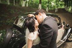 Happy newlywed couple, man and wife kissing near stylish retro car Royalty Free Stock Image