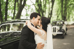 Happy newlywed couple, man and wife kissing near stylish retro car Stock Photo