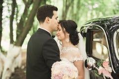 Happy newlywed couple, man and wife kissing near stylish retro car Royalty Free Stock Photography