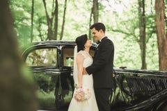 Happy newlywed couple, man and wife kissing near stylish retro car Royalty Free Stock Photos