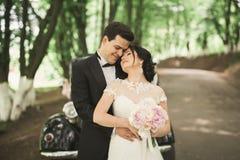 Happy newlywed couple, man and wife kissing near stylish retro car Stock Image