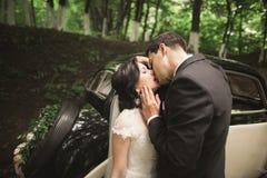 Happy newlywed couple, man and wife kissing near stylish retro car Stock Images