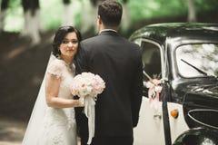 Happy newlywed couple, man and wife  near stylish retro car Stock Photos