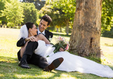 Happy newlywed couple relaxing in park Stock Photo