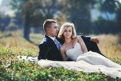 Happy newlywed couple relaxing & posing in a field at sunset Stock Images
