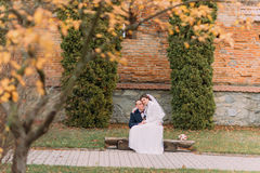 Happy newlywed couple sitting on bench in autumn park. Bride is leaning to her new husband shoulder Stock Photos