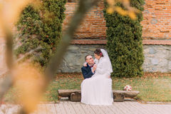 Happy newlywed couple sitting on bench in park holding hands together Stock Photography