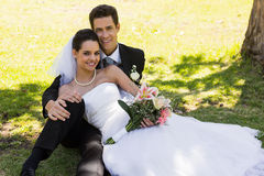 Happy newlywed couple sitting in park Royalty Free Stock Photography