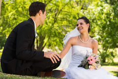 Happy newlywed couple sitting in park Royalty Free Stock Image
