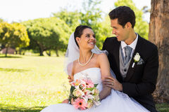 Happy newlywed couple sitting in park Stock Photo
