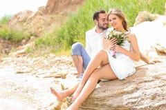 Happy newlywed couple sitting. On rocky beach Stock Image