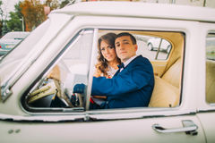 Happy newlywed couple sitting in vintage car. Groom's hands are on handlewheel Royalty Free Stock Image