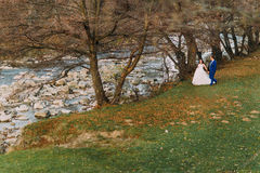 Happy newlywed couple strolling on rocky pebble river bank with trees and stream as background Royalty Free Stock Photography