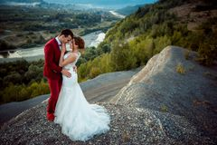 Happy newlywed couple is tenderly hugging at the edge of the mountains at the background of the magnificent landscape of. River and forests Stock Photography