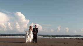 Happy newlywed couple walking on the beach stock video