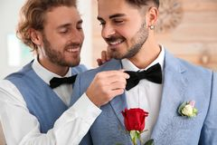 Happy newlywed gay couple with flower royalty free stock photography