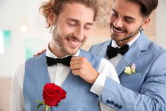 Happy newlywed gay couple with flower royalty free stock images