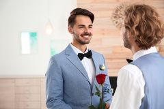 Happy newlywed gay couple with flower stock photos