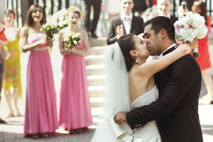 Happy newlywed married couple husband and bride kissing near arb Royalty Free Stock Photo