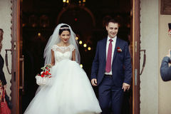 Happy newlywed romantic couple coming out of church after weddin Stock Photography