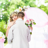 Happy newlywed romantic couple dancing at wedding aisle with pink decorations and flowers Stock Photography