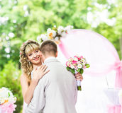 Happy newlywed romantic couple dancing at wedding aisle with pink decorations and flowers Stock Photos