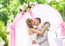 Happy newlywed romantic couple kissing at wedding aisle with pink decorations and flowers Stock Photo