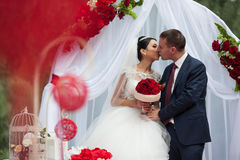Happy newlywed romantic couple kissing at wedding aisle with red Stock Images