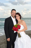 Happy Newlyweds. Bride and Groom Smiling at the Beach with a red rose bouquet Stock Image