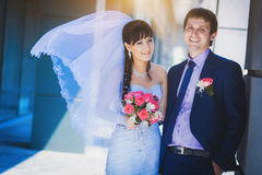 Happy newlyweds against a blue modern building. Background Stock Image