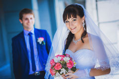 Happy newlyweds against a blue modern building Royalty Free Stock Images